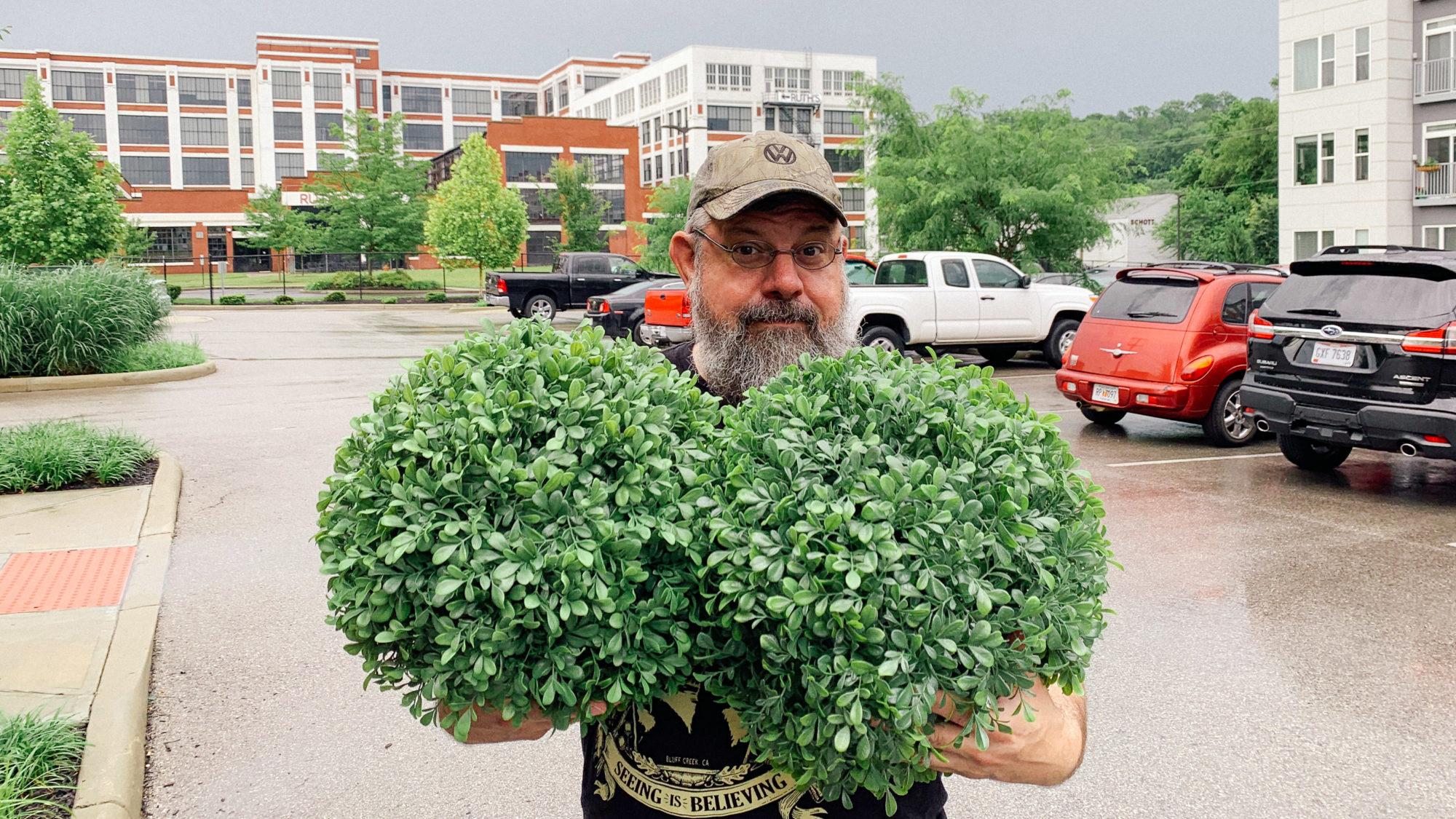 Jim Corbett of St. Louis holding two fake shrubberies