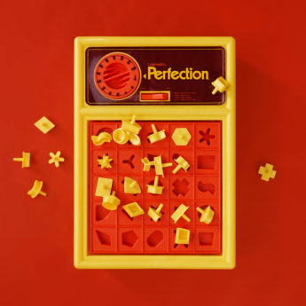 Perfection Game with pieces strewn about