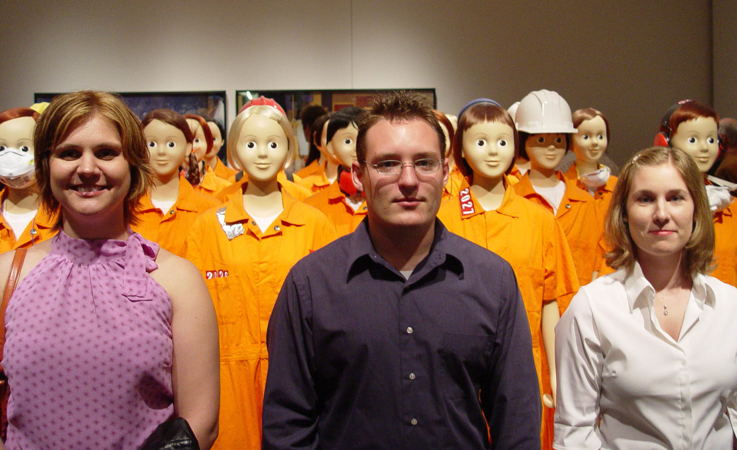 3 people in front of mannequins wearing orange jumpsuits