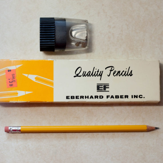 A box of Quality brand pencils, a pencil sharpener, and a pencil