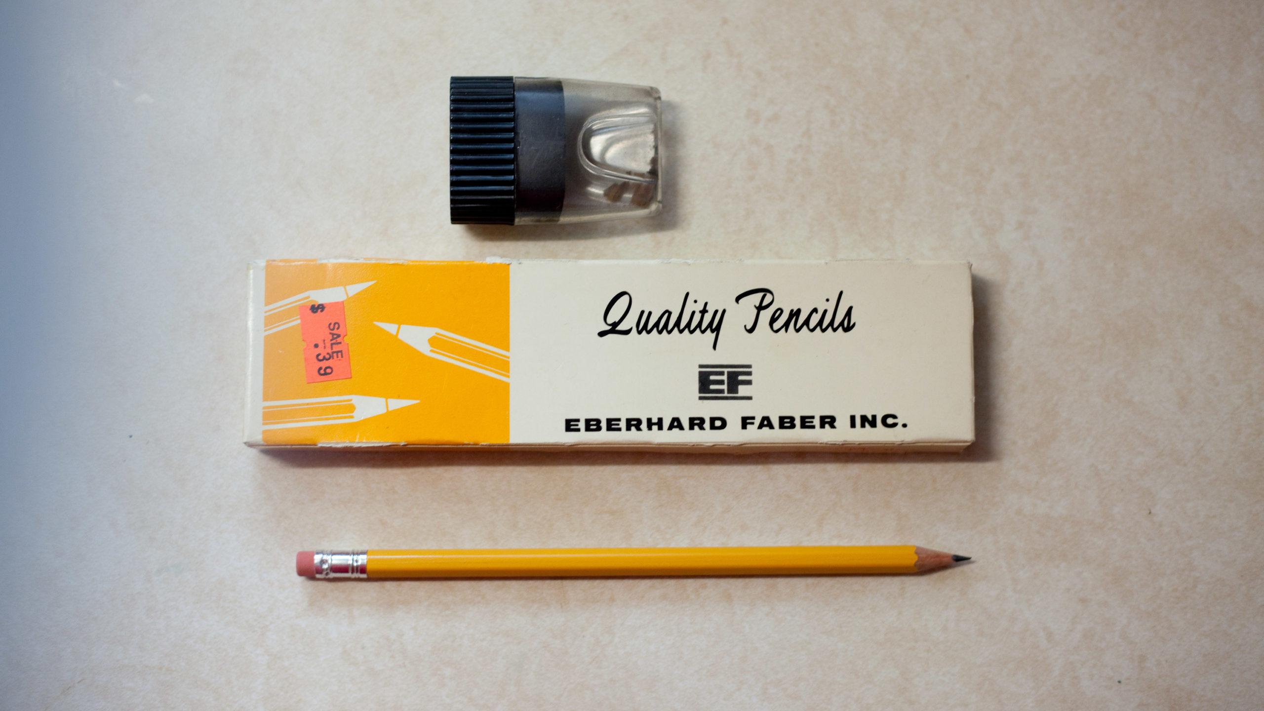 A box of Quality brand pencils, a pencil sharpener, and a pencil
