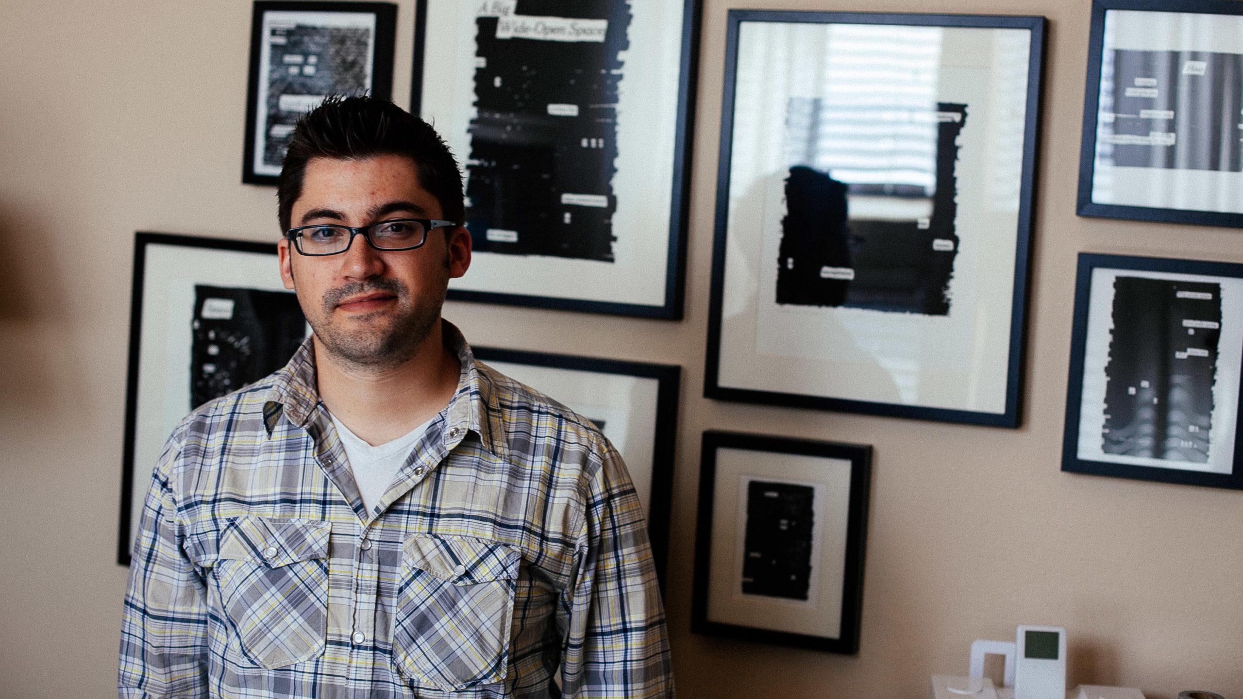 A man in front of framed artwork