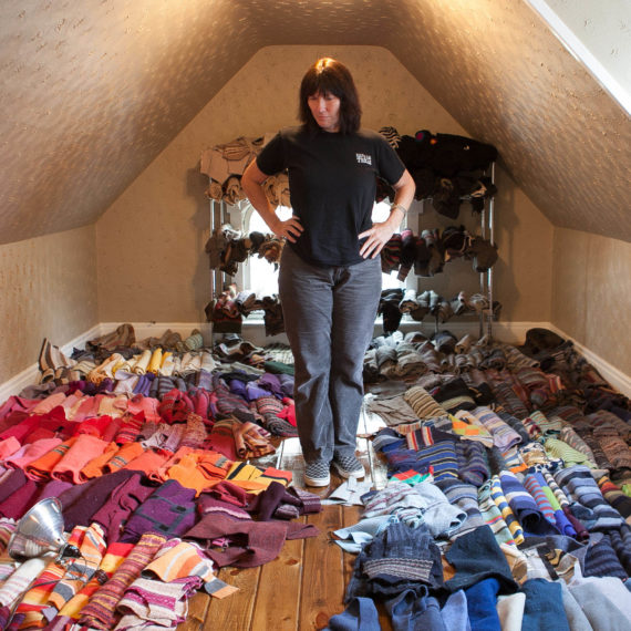 Kelley Deal surrounded by sweaters