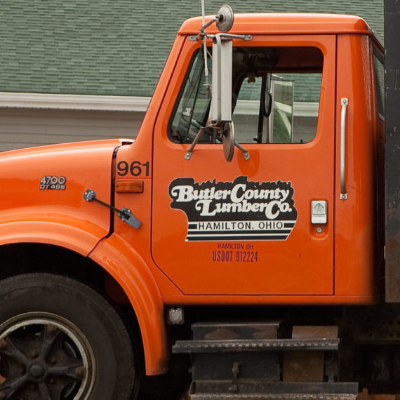 Orange truck with a logo set in a swash typeface