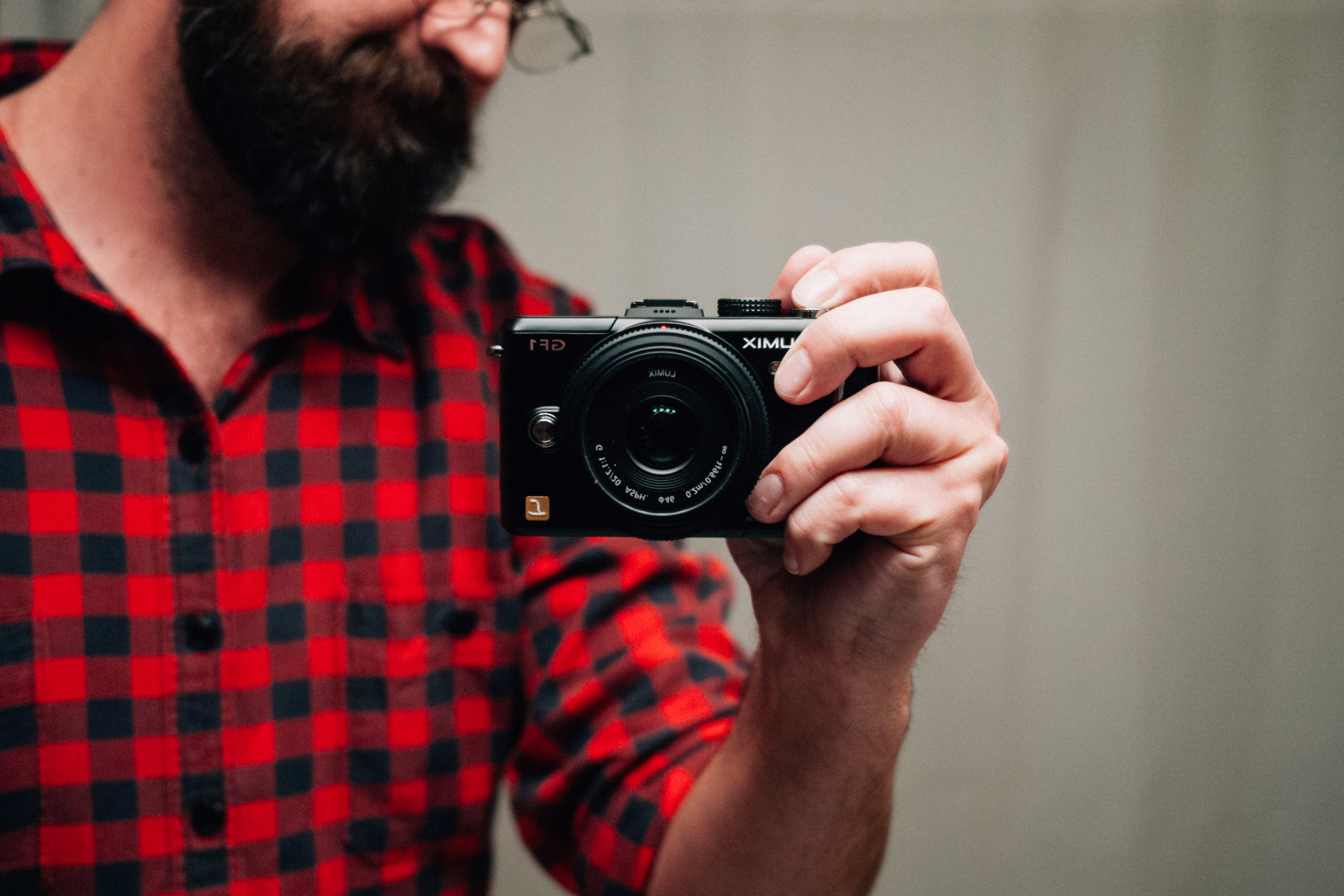 Man in buffalo check shirt holding a camera and taking a selfie in the mirror