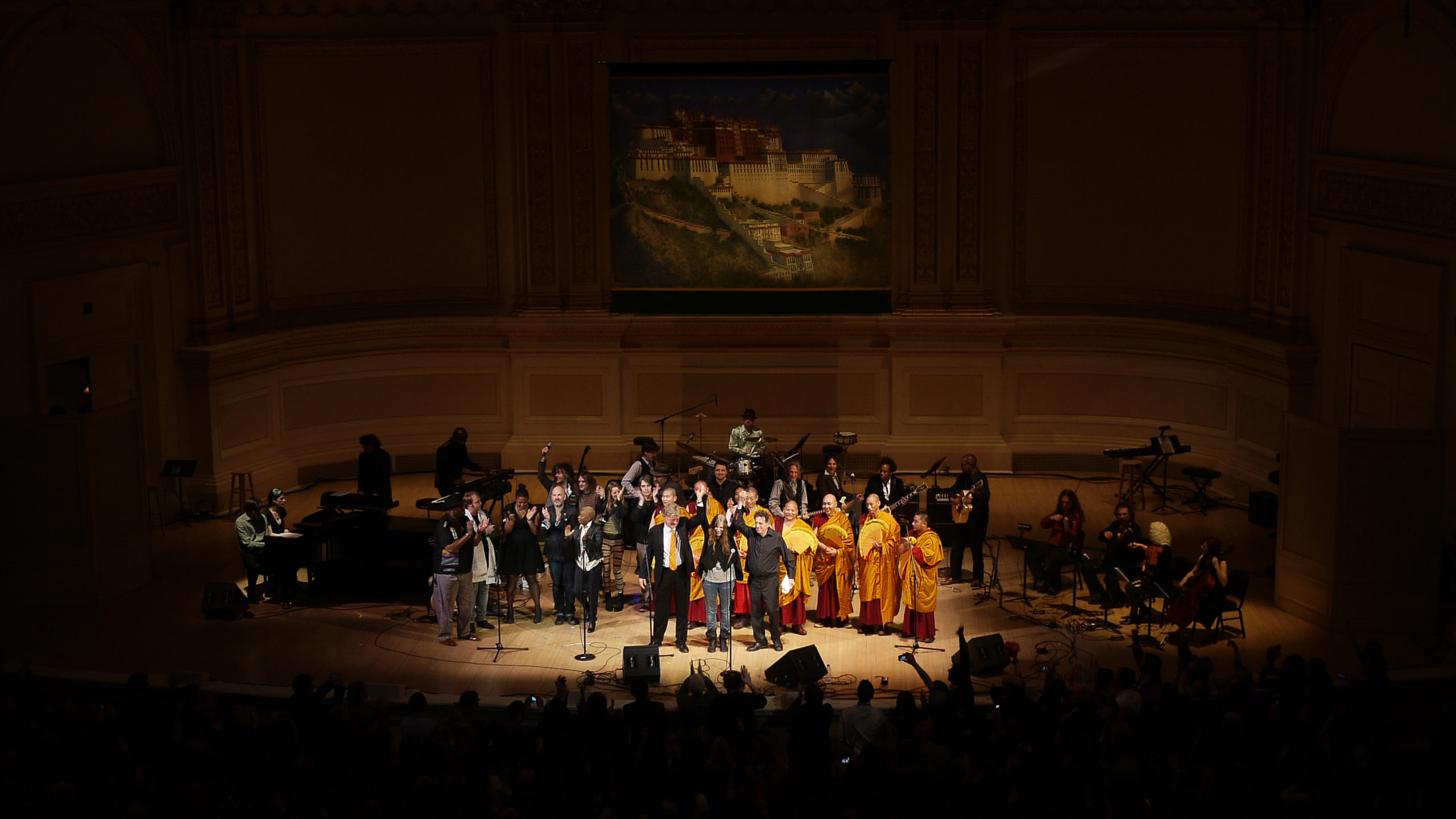 Patti Smith, Robert Thurman and Philip Glass bow among other performers on the stage of Carnegie Hall