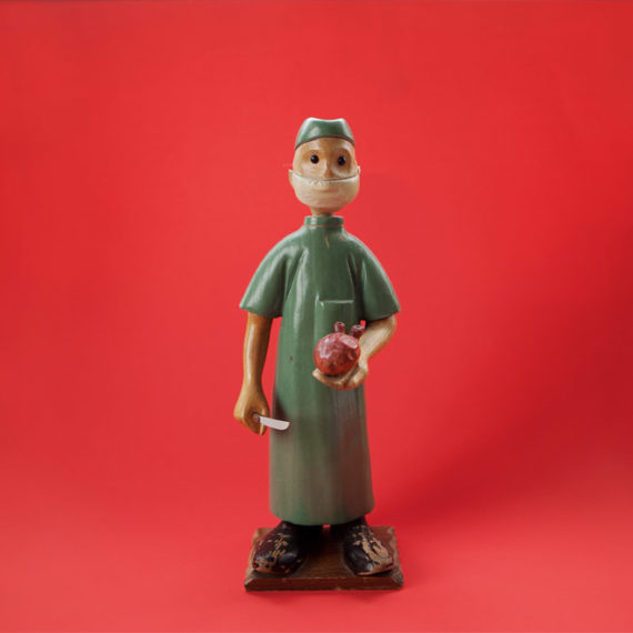 A wooden figure of a doctor on a red background