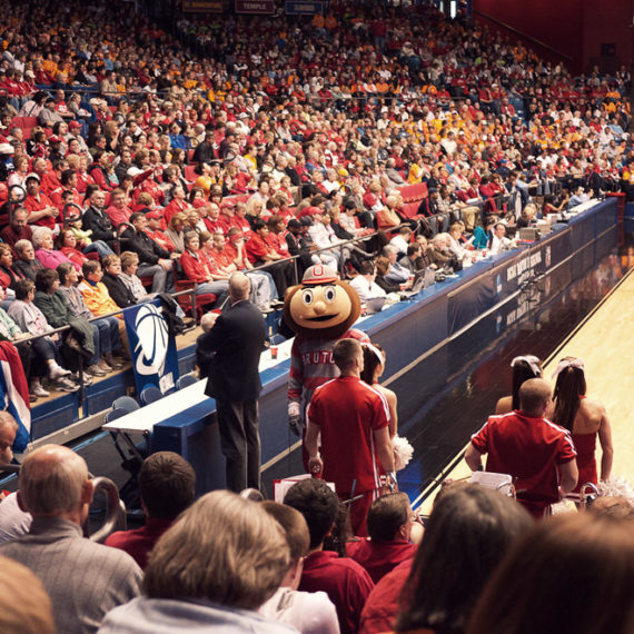 Brutus the Buckeye, the Ohio State mascot on a basketball court in a filled stadium