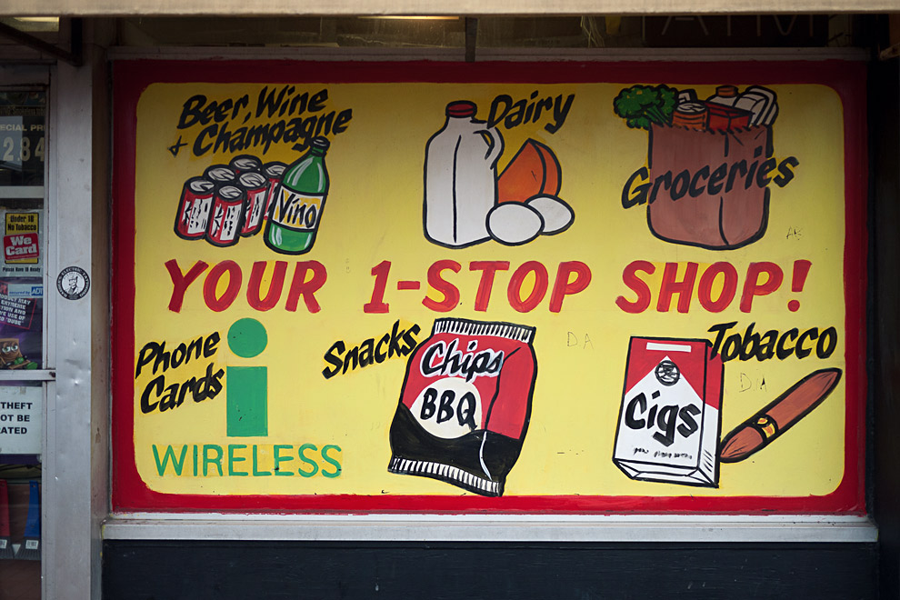 """A sign in the window of a store that reads """"Your 1-Stop Shop"""""""