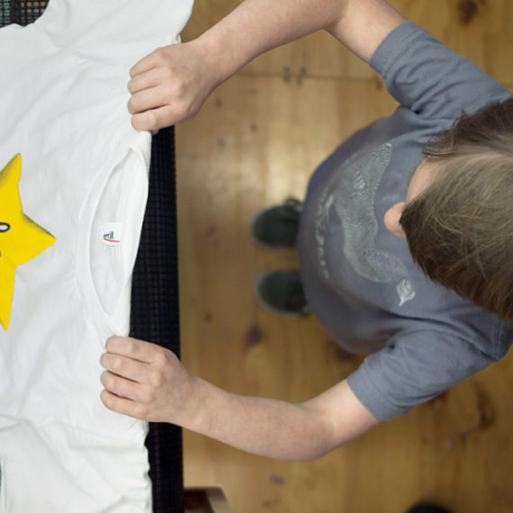 pulling a shirt with a star design off a screen printing dryer