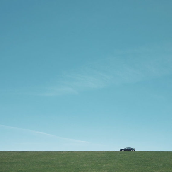 a Ford Edge on top of a green bit of land with a bunch of blue skies above