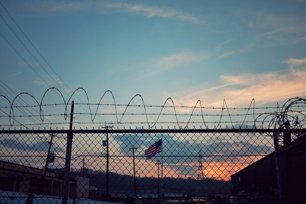 Barbed wire fence and sunset with American flag