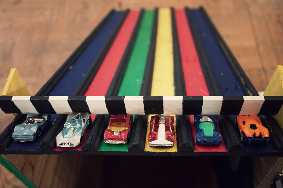 Toy cars about to race down a colorful track