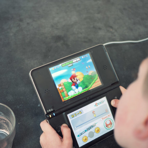 A young man plays Mario on a Nintendo DS