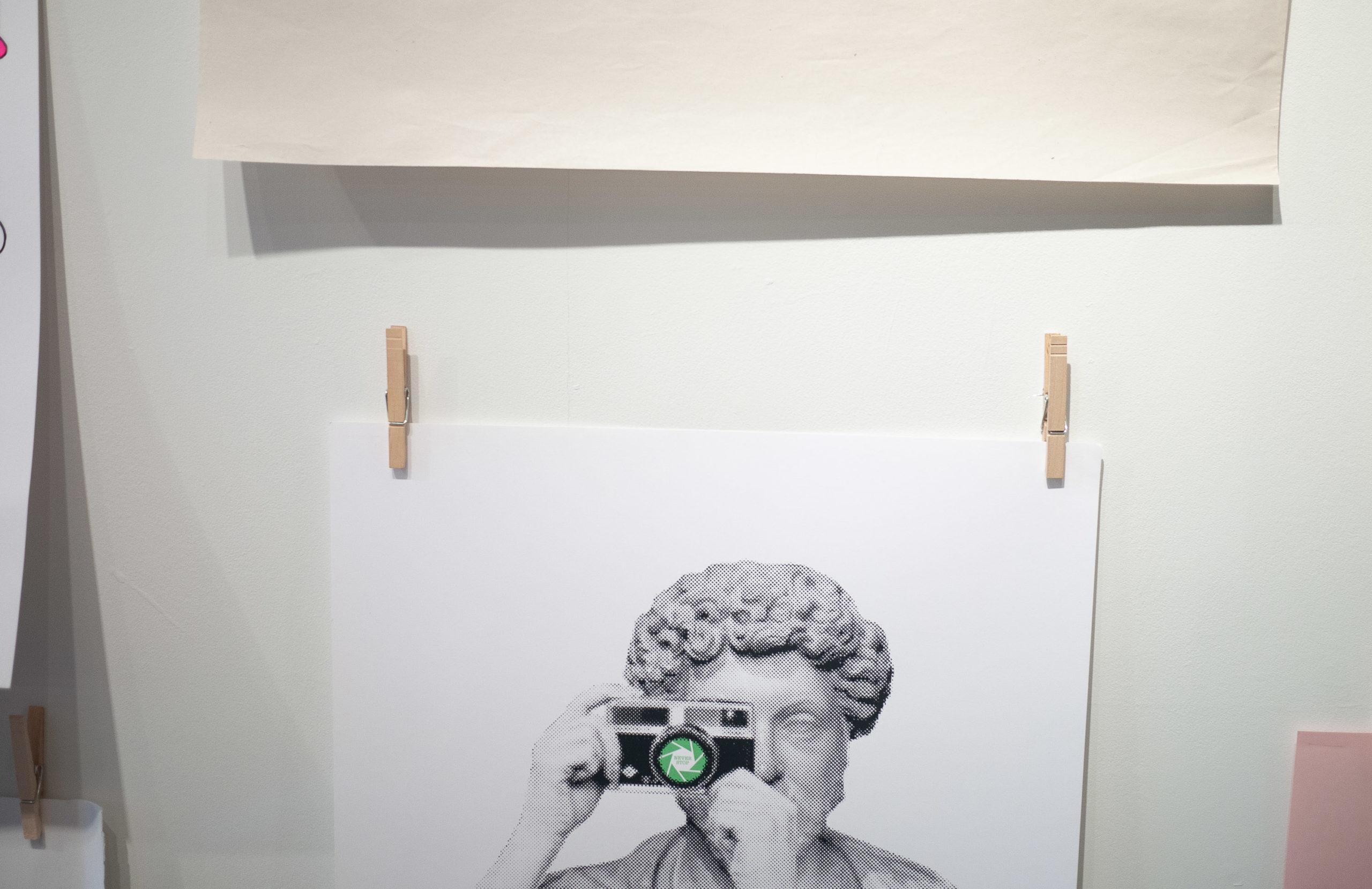 A screen printed poster of venus de milo holding a camera