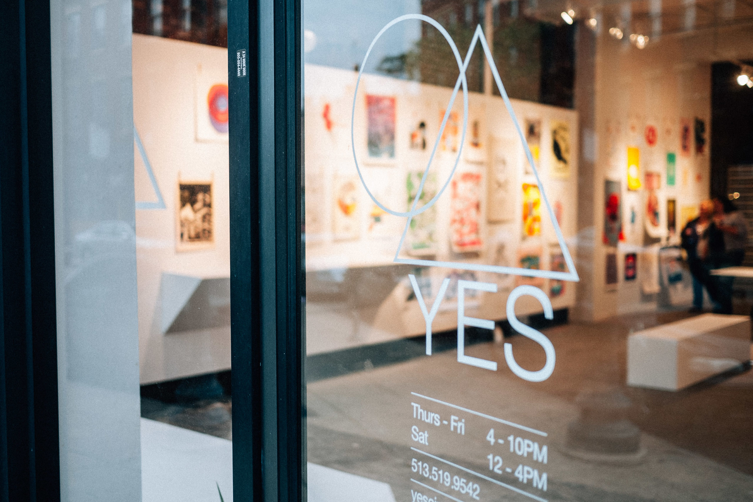 A gallery with the word YES on the door with a circle and triangle