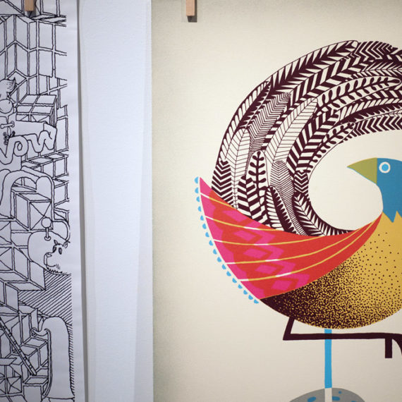 Detail of screen printed posts on a wall, one abstract and one of a bird