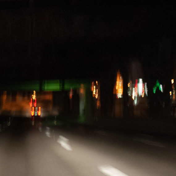 blurry photo driving on bridge at night