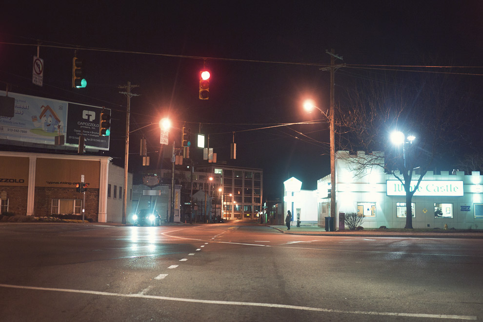 An intersection at night with a red light and White Castle