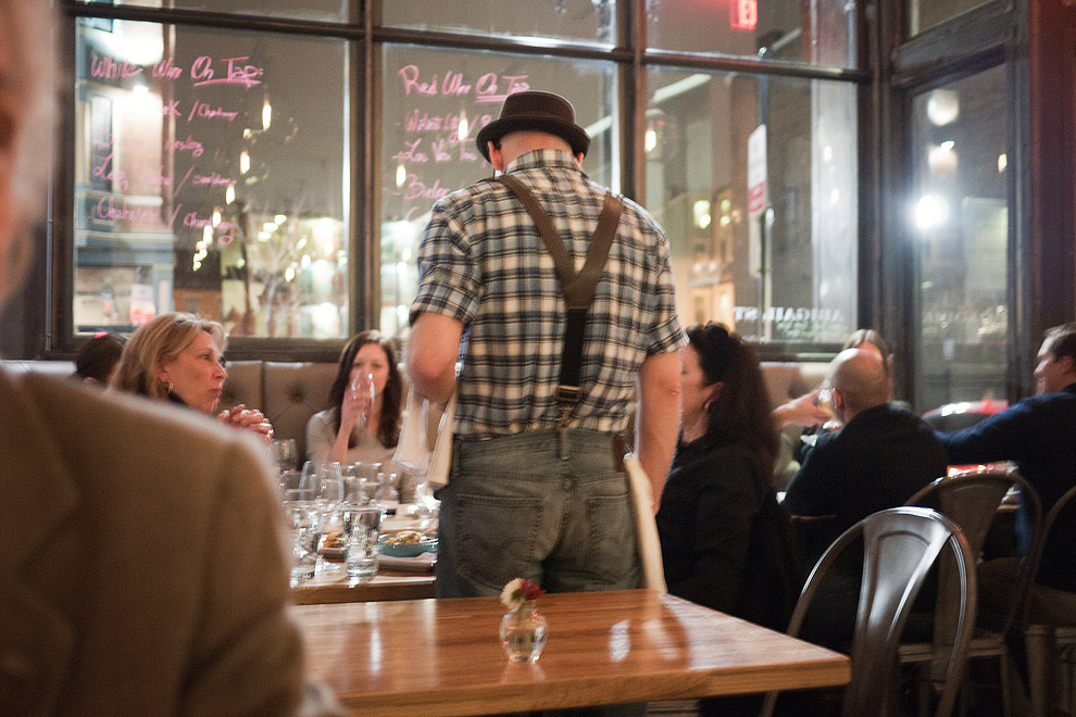 A server in suspenders waits on a table