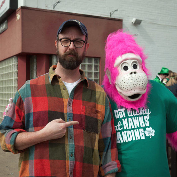 bearded man pointing at person in pink gorilla suit