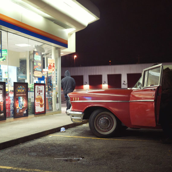 A classic car at night in front of a convenience store