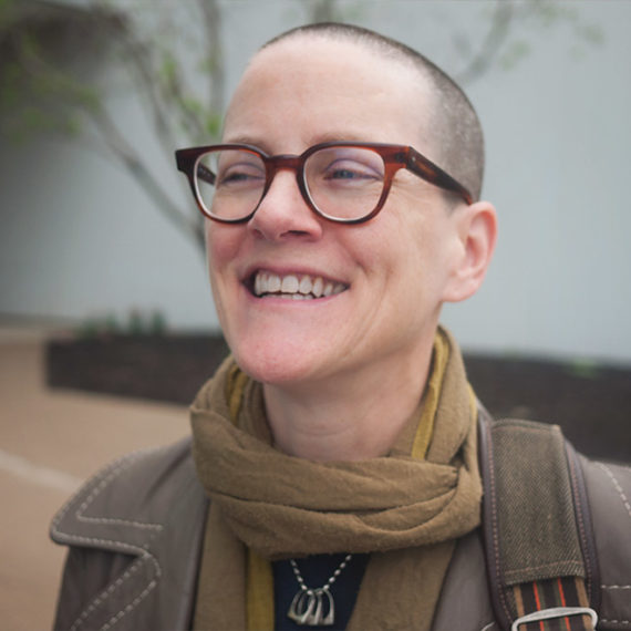 A woman with short hair, glasses, a scarf and a wonderful smile