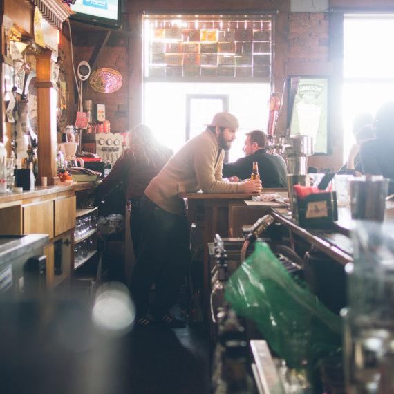 A bartender leans on the bar, taking a break