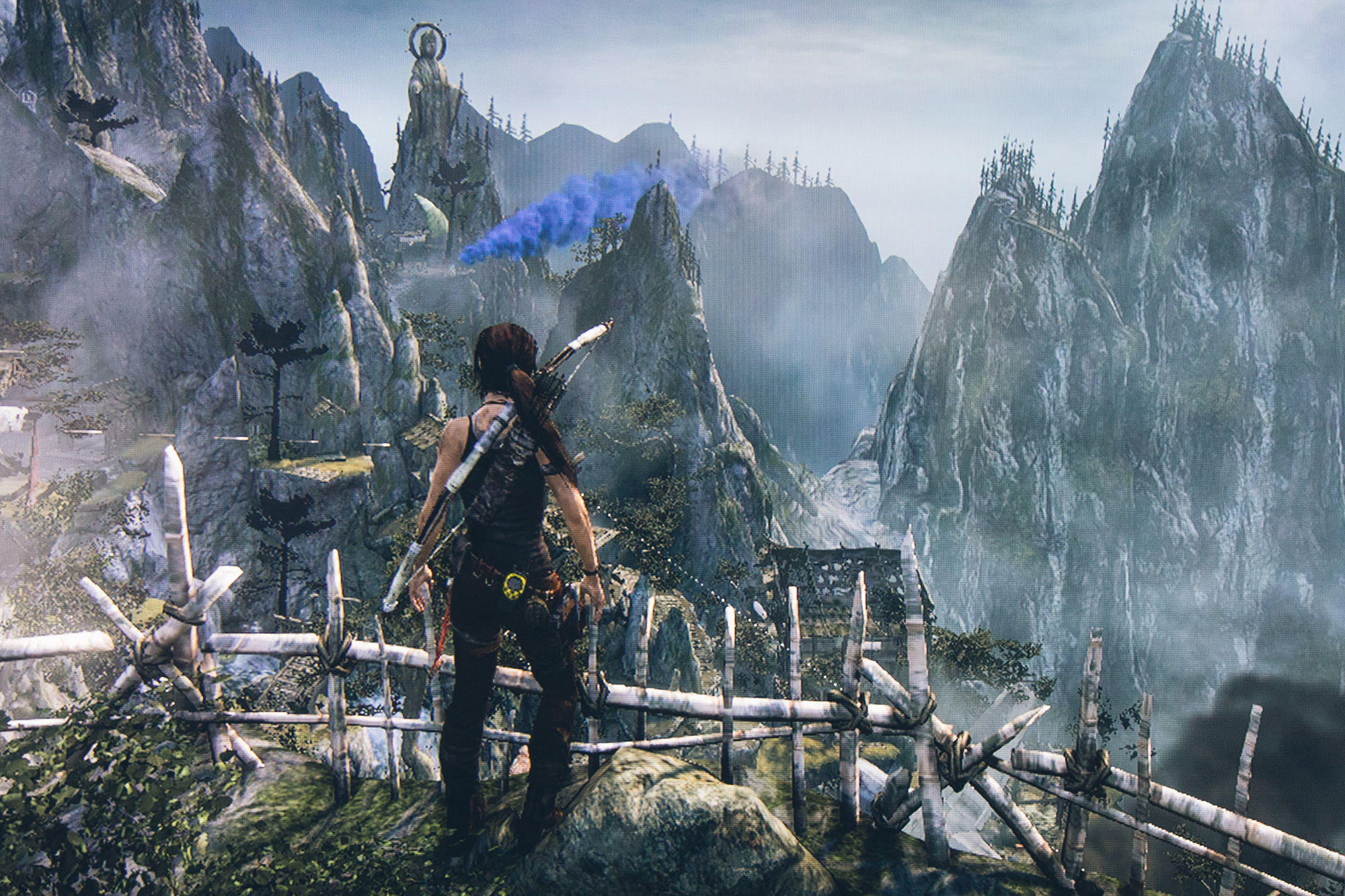 In this screenshot of an adventure third person videogame, a woman looks out over rugged mountains at the path ahead