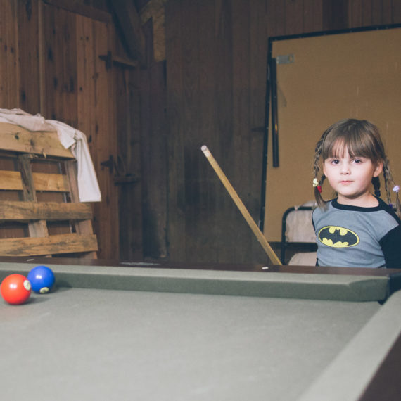 a young girl at a pool table