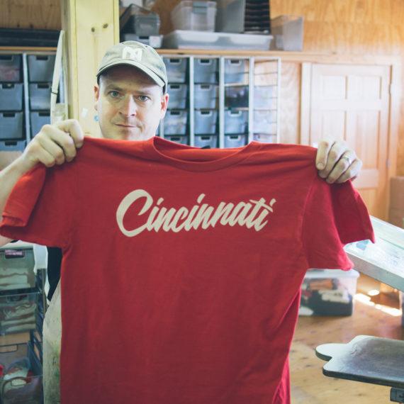 A man holds up a t-shirt that has Cincinnati written on it