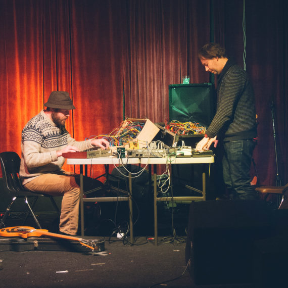 Two musicians perform on stage fiddling with electronic equipment