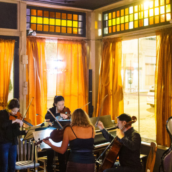 a quartet performs in the corner windows of a small bar