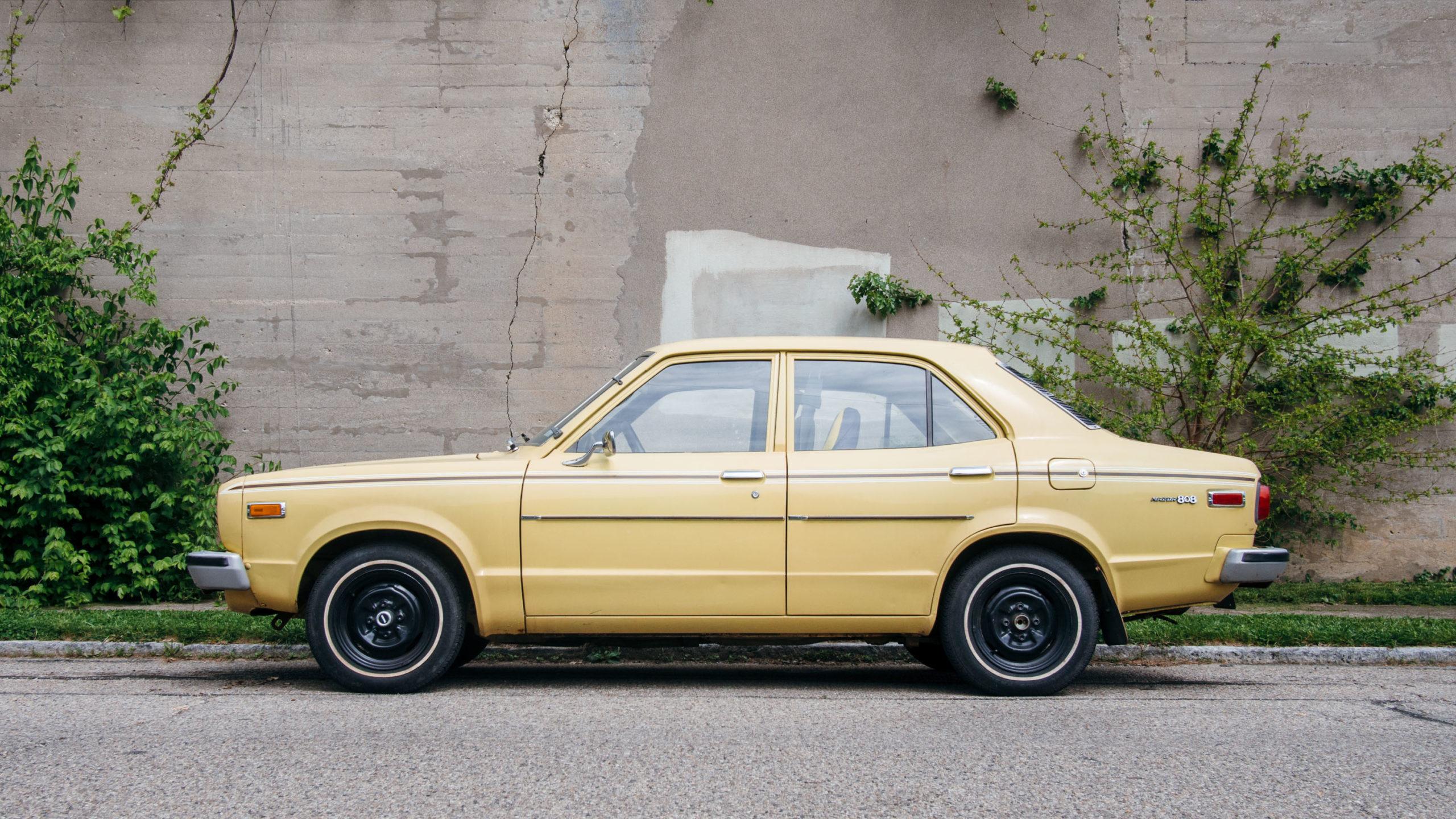 an old yellow Mazda car