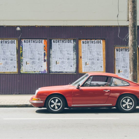 Classic red Porsche in front of a building behind rehabbed