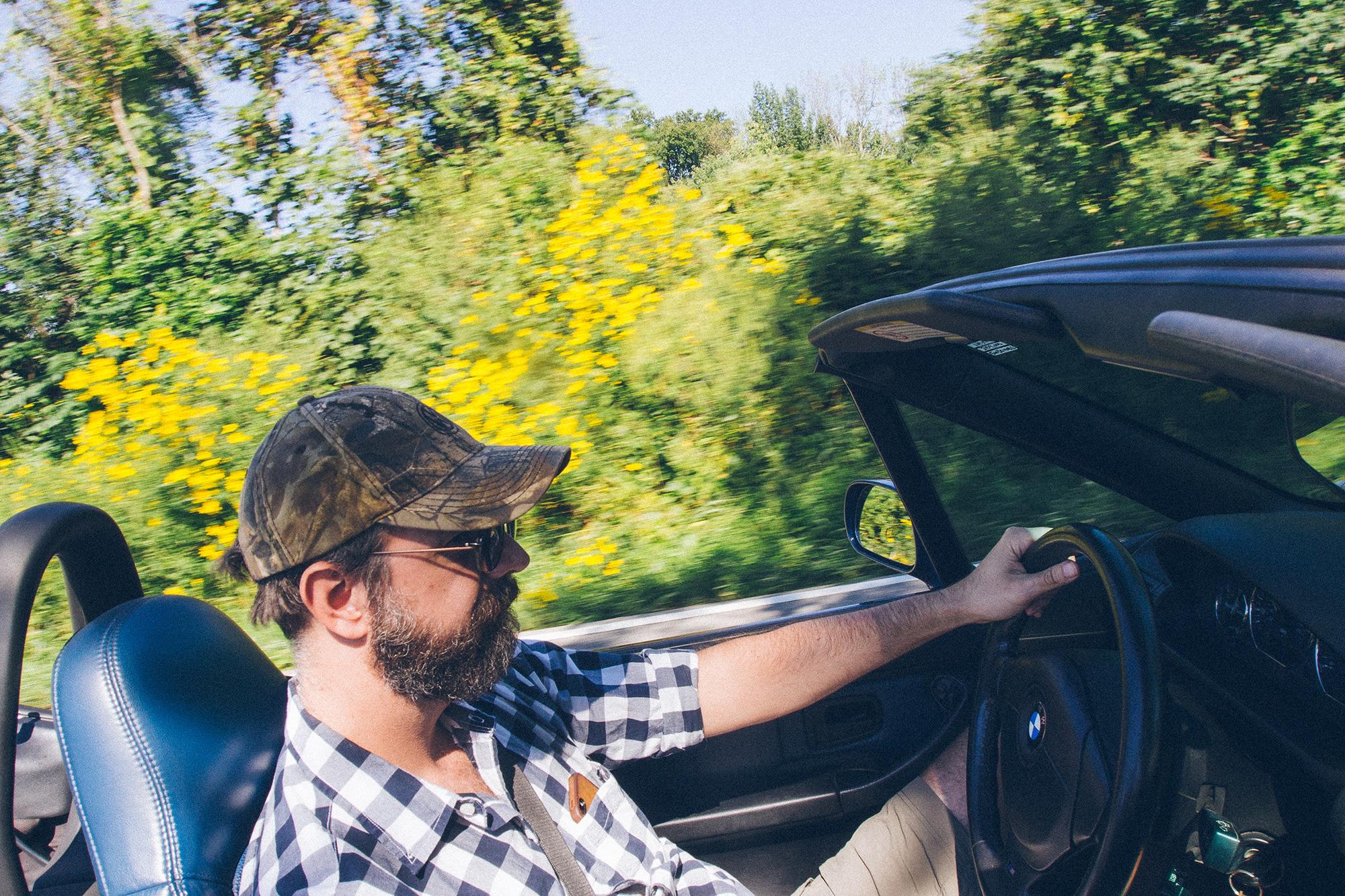 A man driving a convertible