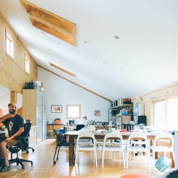 Two men at desks in a light filled studio
