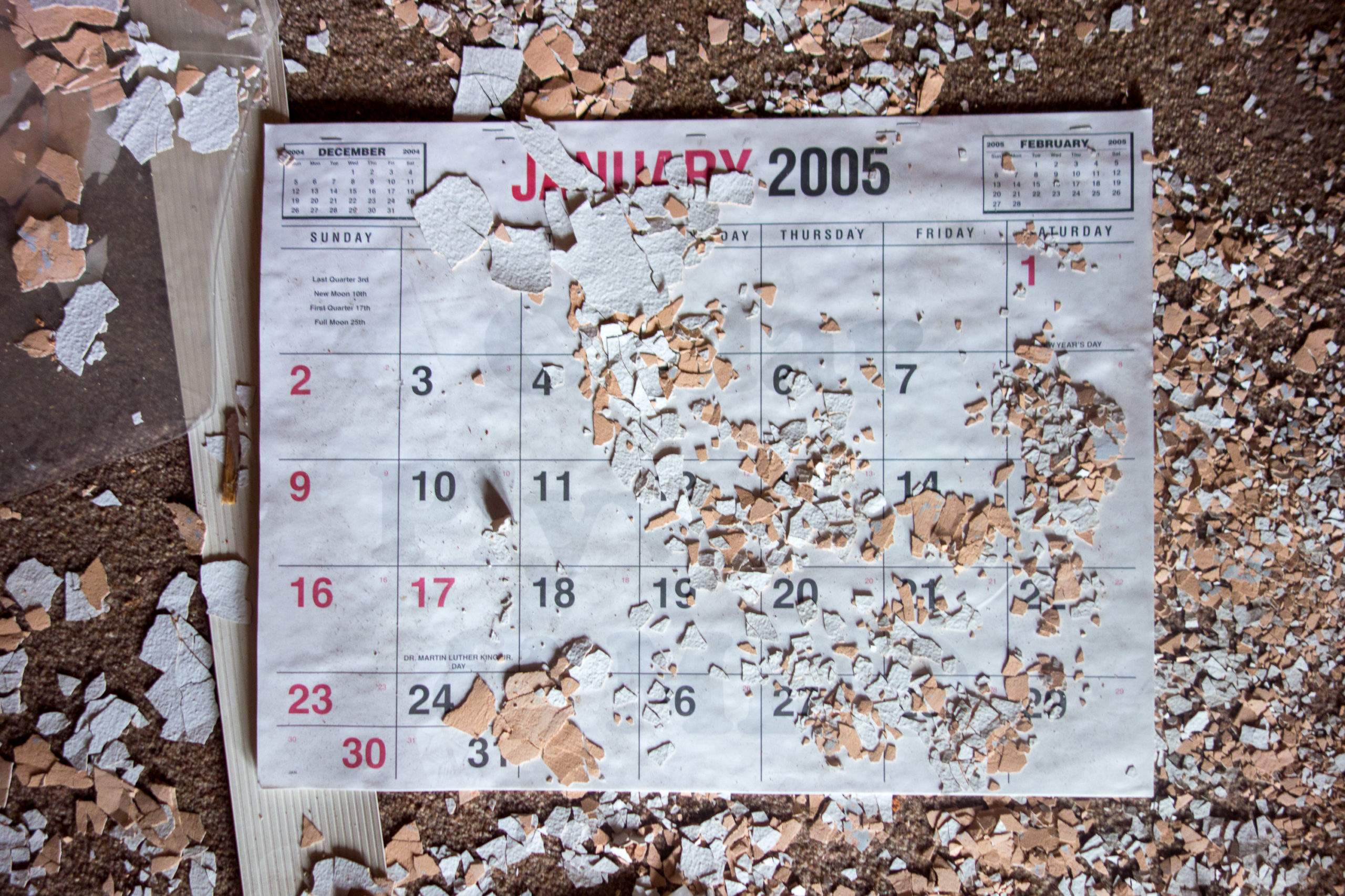 A January 2005 calendar on a floor covered in paint chips