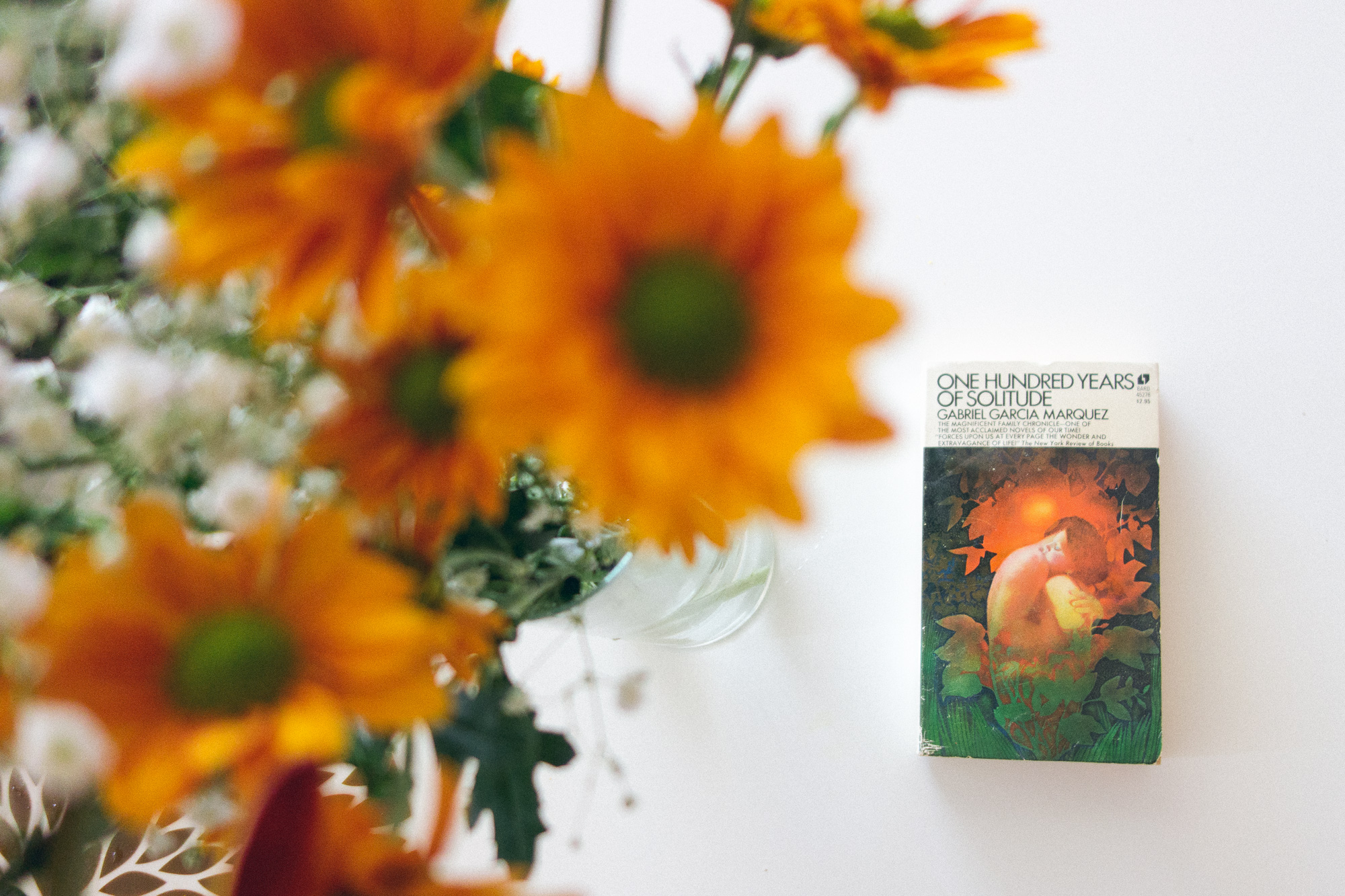 100 Years of Solitude book and some orange flowers