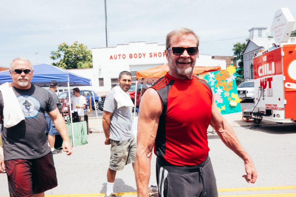A man in a red shirt walks through a sunny day at a street fair