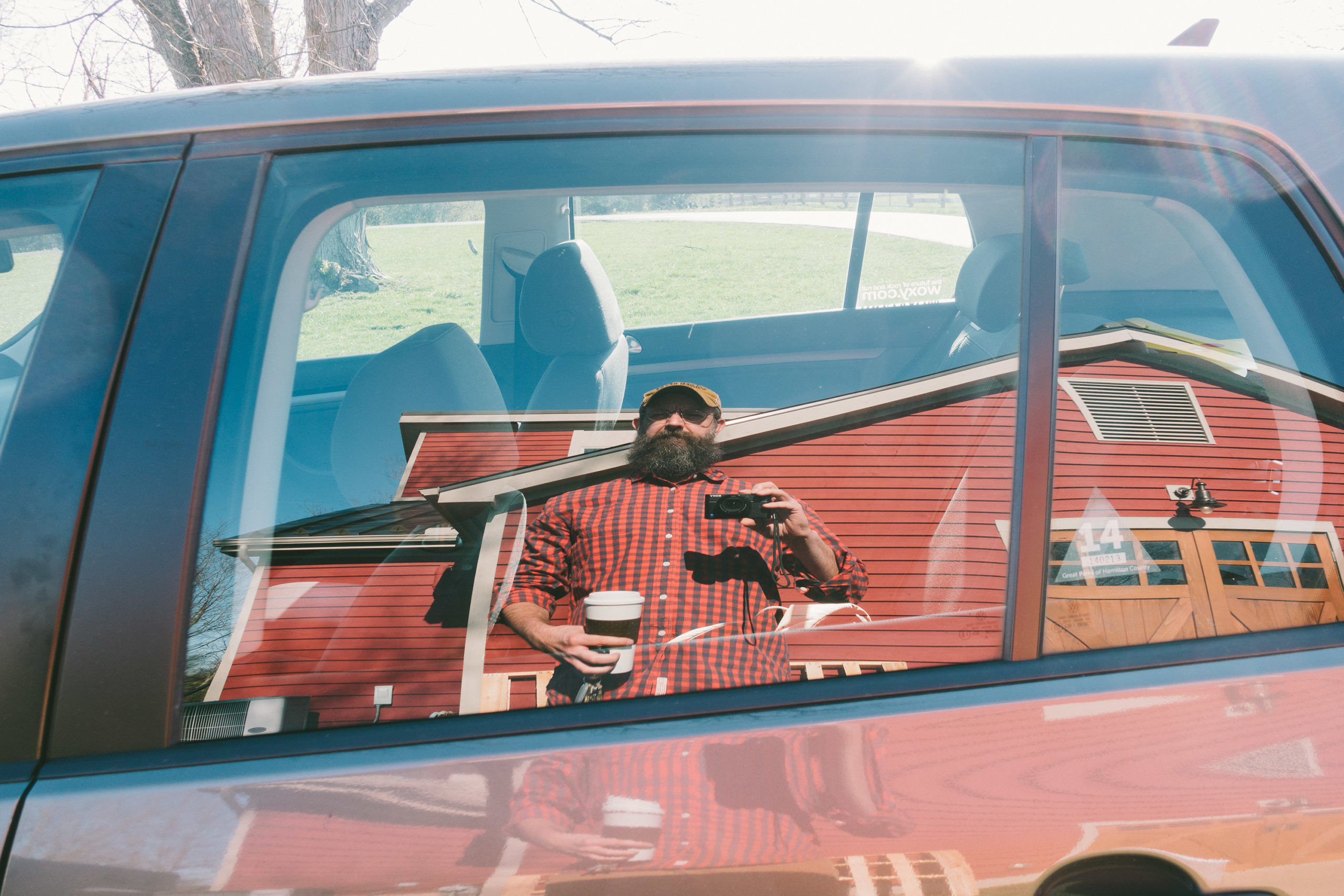 A man taking a selfie in the reflection of a car window