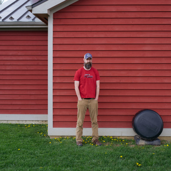 A man in a red shirt standing in front of a red barn
