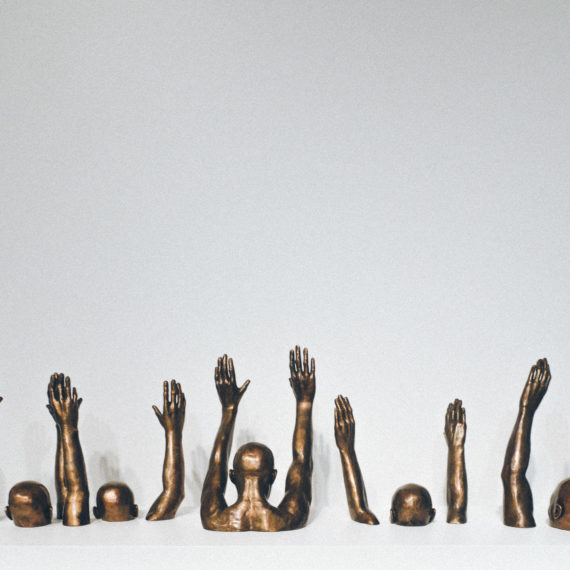A sculpture of black folks with their hands raised
