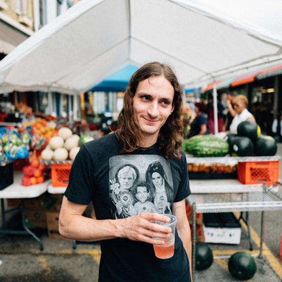 A man with long hair stands at an outside market with a drink in his hand