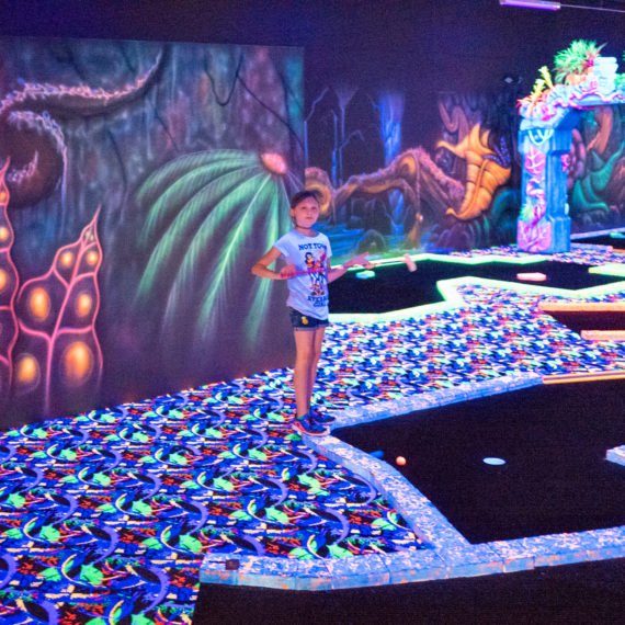 A young woman plays miniature golf in a blacklit course