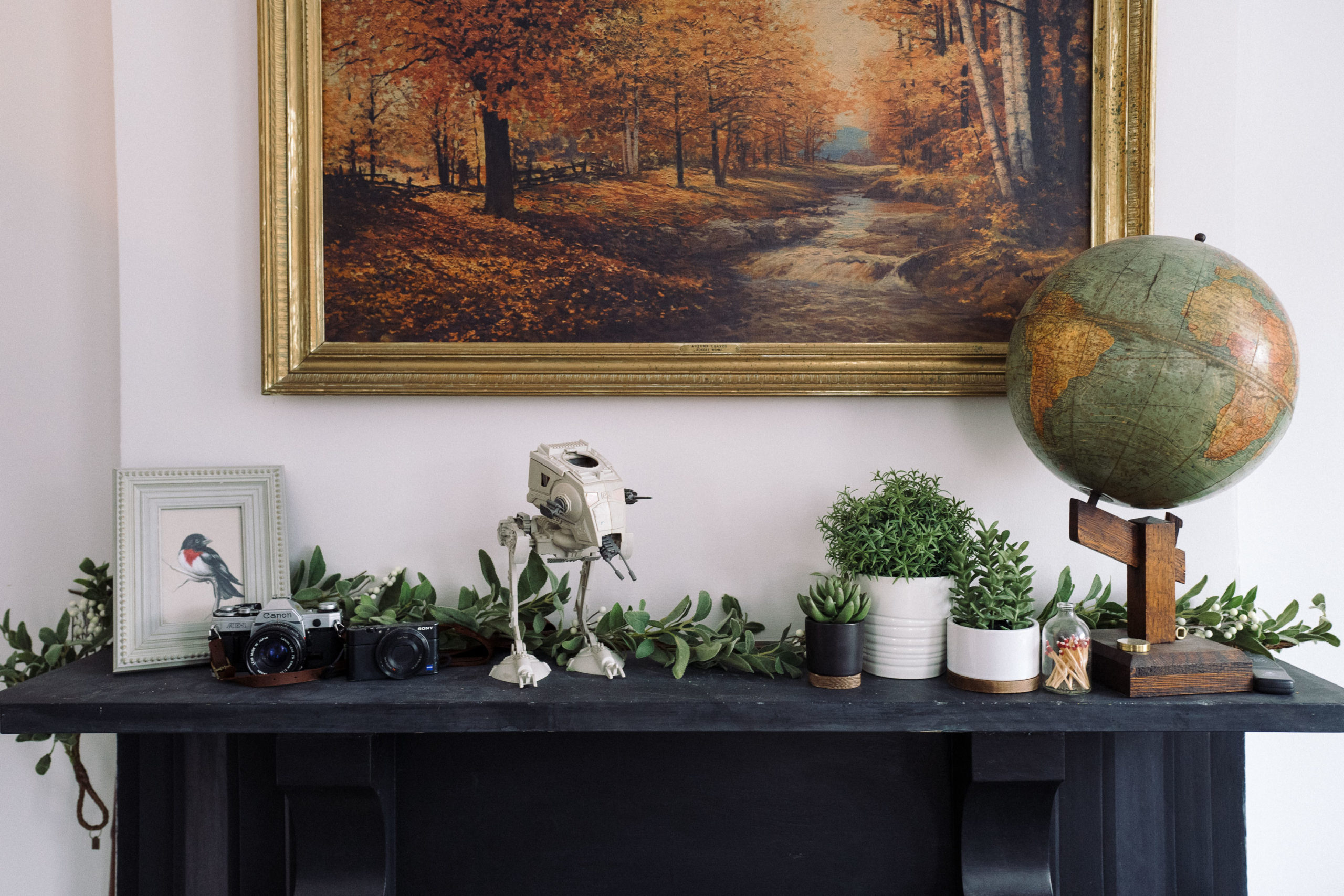 A mantle with some Christmas greenery that is fake