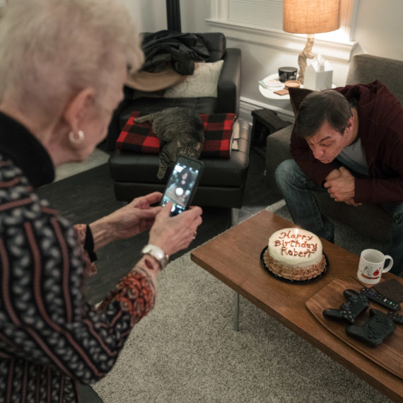 A woman taking a photo of a man blowing out birthday candles