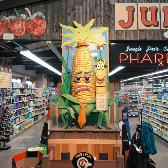 A large anthropomorphized piece of corn in a grocery store