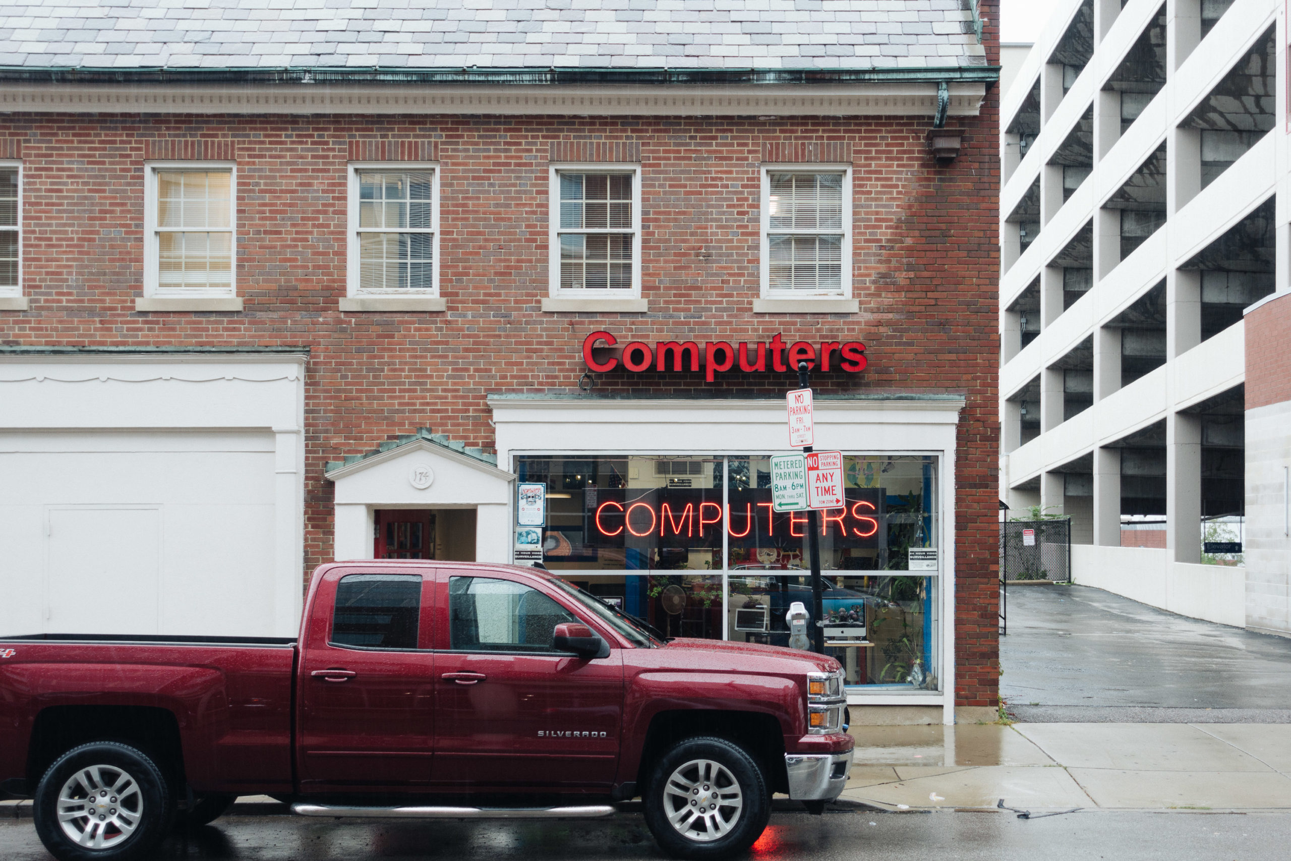 A neon computers sign in the window of a store with a pickup truck driving by