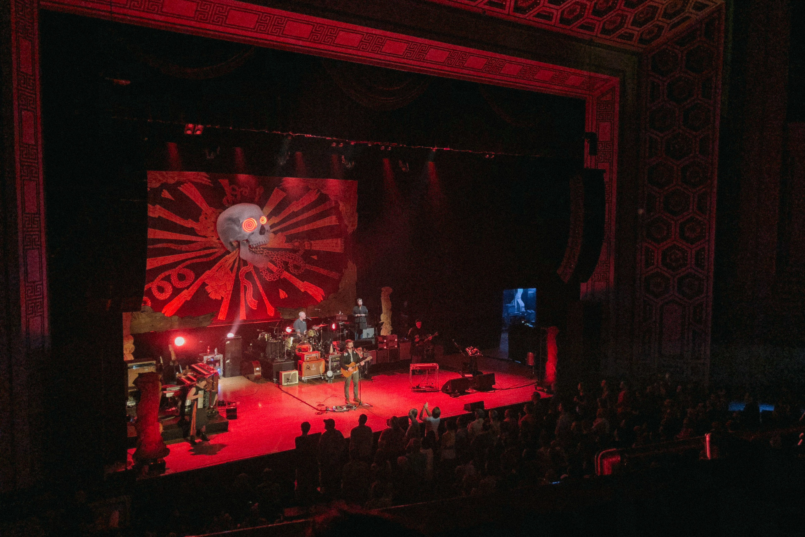A band playing on stage bathed in red light